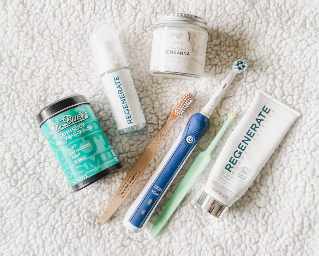 A flat lay of dental care products including toothbrushes, toothpaste, mouthwash and dental floss.