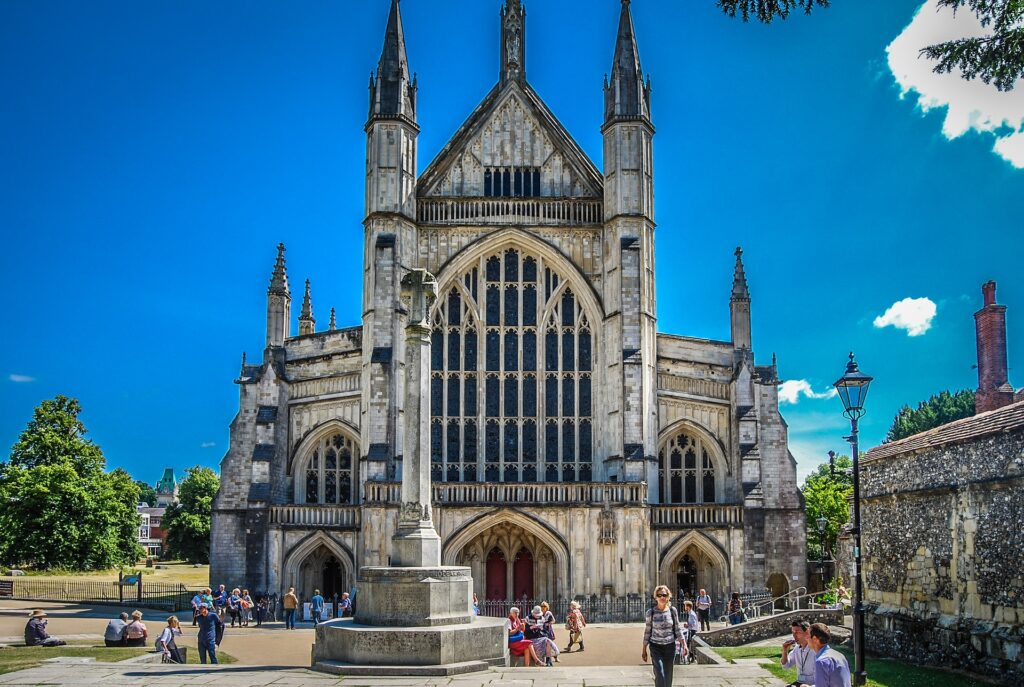 A view of the front of Winchester Cathedral on a sunny day.