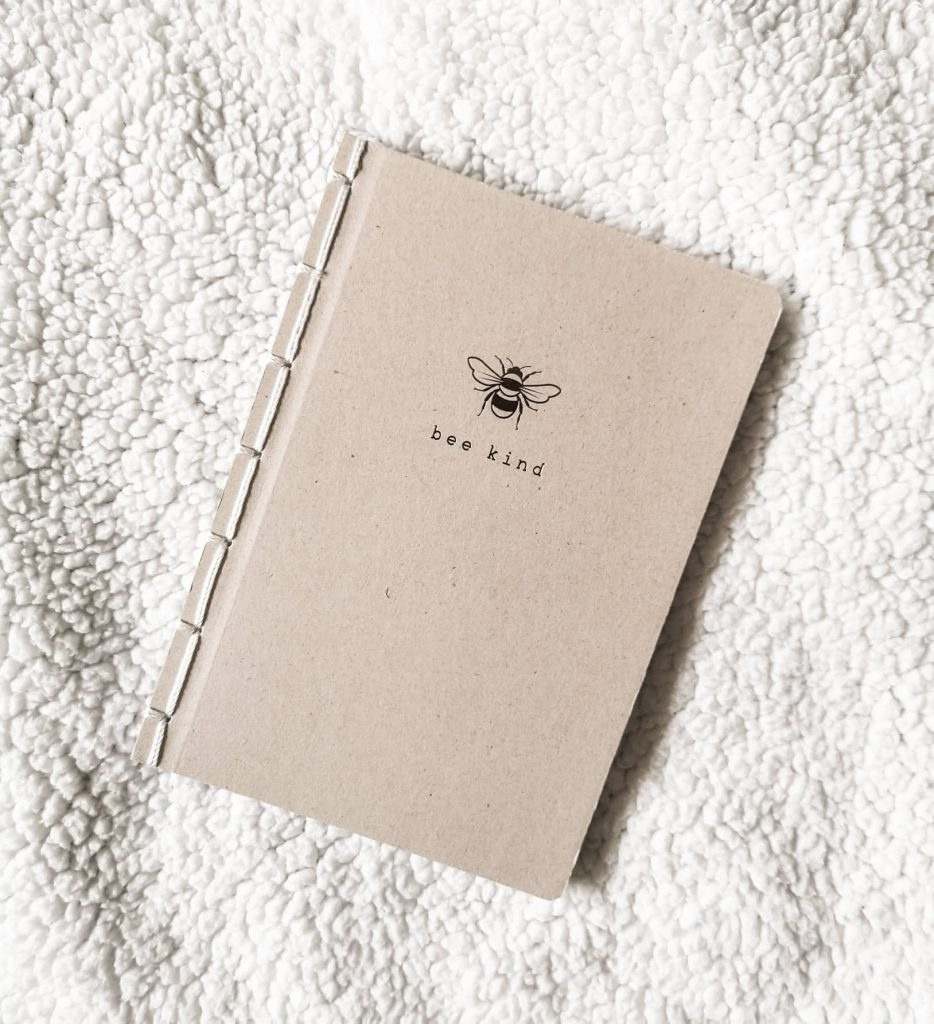A notebook made of recycled board and bound with string. It features a bee and the words 'bee kind'.