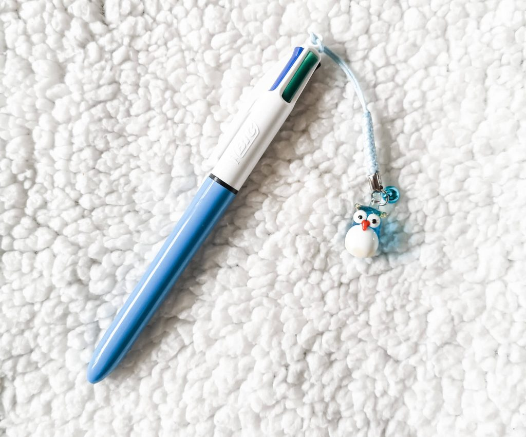 A BIC 4 colour original retractable ballpoint pen with an owl charm attached to the end.