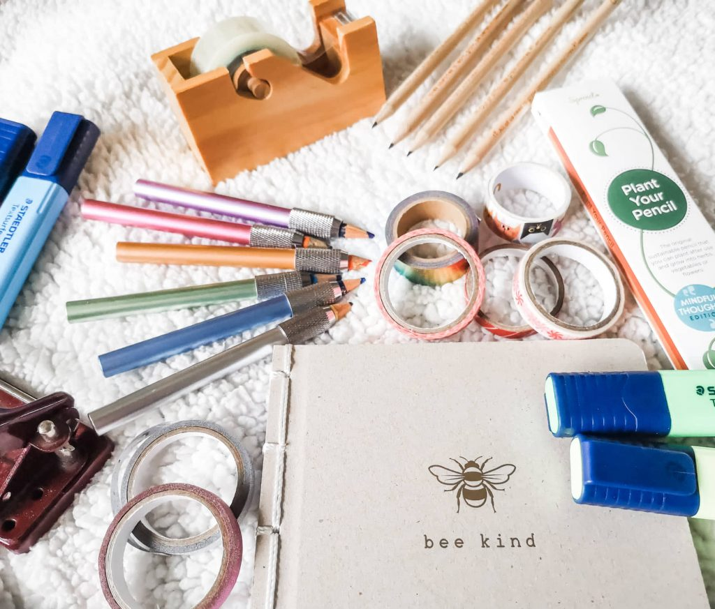 A flatlay of stationery including pencil extenders, washi tape, highlighters, pencils and a wooden tape dispenser.