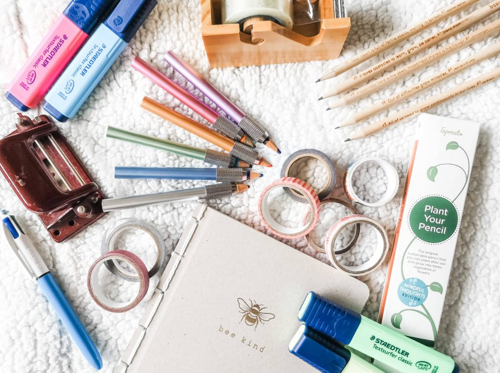 A flatlay of sustainable stationery including washi tape, pencil extenders, highlighters and a notebook.
