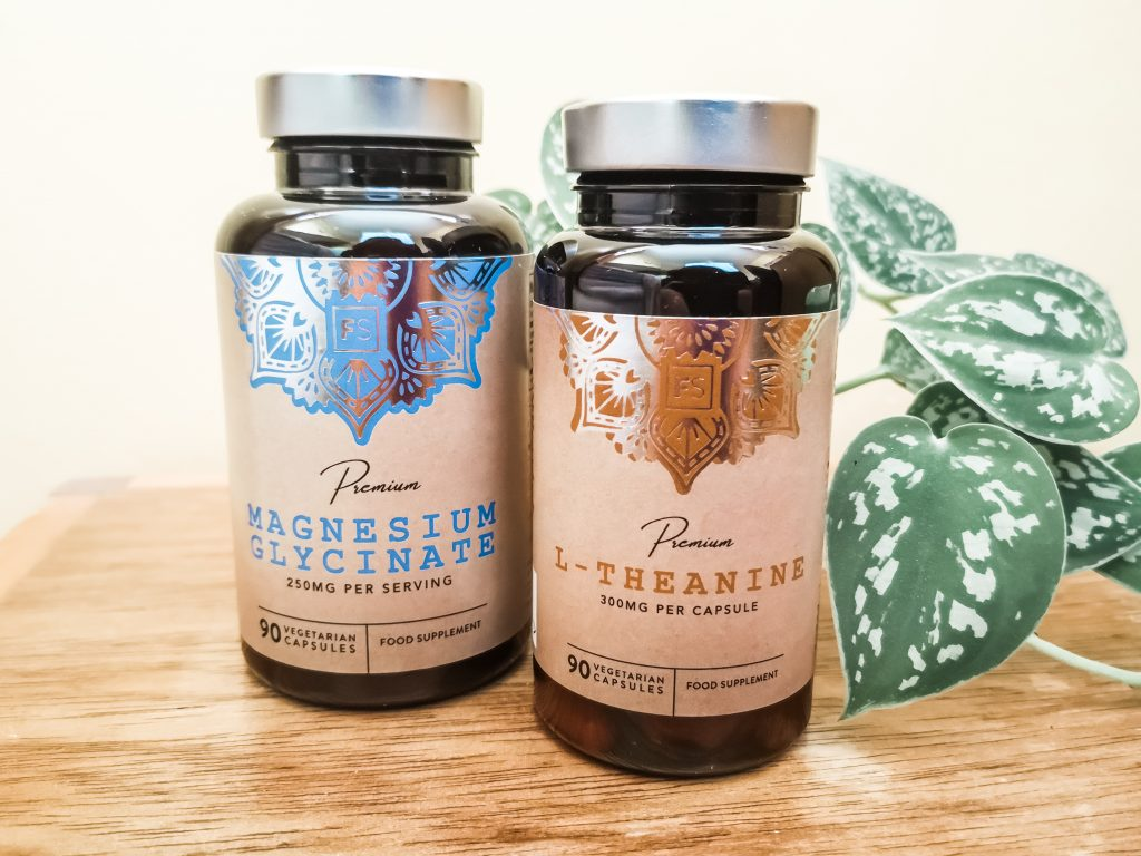 Two bottles of supplements (L-Theanine and Magnesium Glycinate) on a wooden surface with a plant in the background
