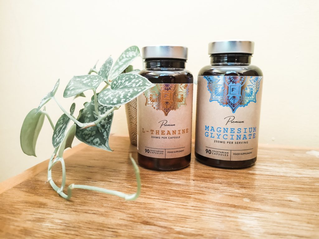 Two bottles of supplements (L-Theanine and Magnesium Glycinate) on a wooden surface with a plant next to them