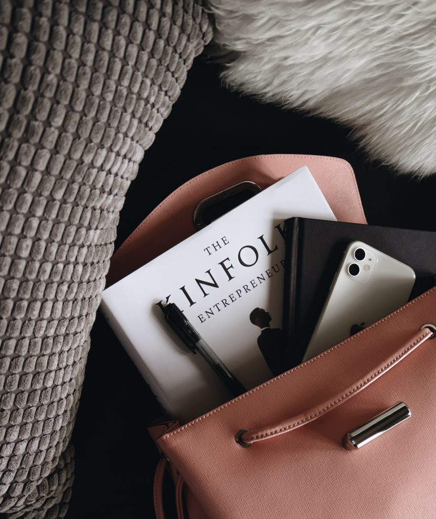 A pink handbag with various items spilling out of it - a phone, notebook, pen and book. The bag is surrounded by grey cushions.