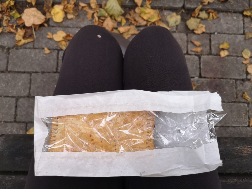 A pasty in a paper bag, resting on a lap. There are fallen leaves on a paved floor in the background.